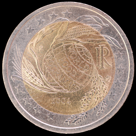 circulated: Commemorative circulated two euro coin isolated on black background. Issued by Italy in 2004 to celebrate World Food Programme, depicting wheat, maize and rice, the basic world sources of nourishment