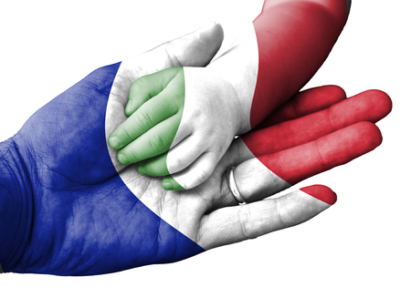 italian politics: France flag overlaid the hand of an adult man holding a baby hand with the flag of Italy overprinted. Conceptual image for help, aid, assistance, rescue. Isolated on white background Stock Photo