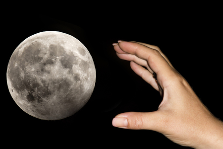 exaggerated: The hand of a woman is taking the moon over a black sky. Conceptual image for aspirations, daydreams, will impossibilities, have exaggerated claims, never being content with what you have Stock Photo