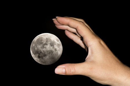exaggerated: The hand of a woman is catching the moon over a black sky. Conceptual image for aspirations, daydreams, will impossibilities, have exaggerated claims, never being content with what you have