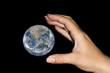 woman handle success: The hand of a woman is catching the earth over a black sky. Conceptual image for control, handling, influence over the world, nature, environment. Elements of this image furnished by NASA