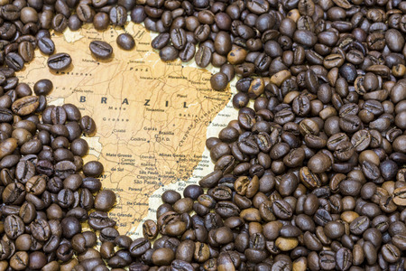exporter: Vintage map of Brazil covered by a background of roasted coffee beans. This nation is the first main producer and exporter of coffee. Horizontal image. Stock Photo