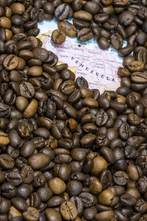 producers: Geographical map of Venezuela covered by a background of roasted coffee beans. This nation is one of the main producers and exporters of coffee. Vertical image.