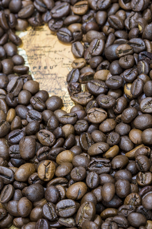 Vintage map of Peru covered by a background of roasted coffee beans. This nation is between the ten main producers and exporters of coffee. Vertical image. Stock Photo