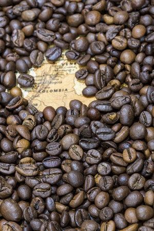exporter: Vintage map of Colombia covered by a background of roasted coffee beans. This nation is the third main producer and exporter of coffee. Vertical image.