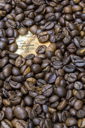 producers: Vintage map of Ecuador covered by a background of roasted coffee beans. This nation is one of the main producers and exporters of coffee. Vertical image. Stock Photo