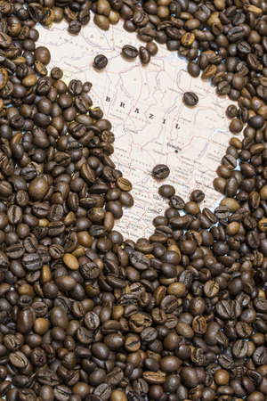 geographical: Geographical map of Brazil covered by a background of roasted coffee beans. This nation is the first main producers and exporters of coffee. Vertical image. Stock Photo