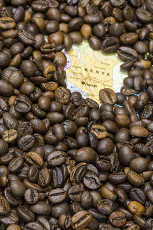geographical: Geographical map of Kenya covered by a background of roasted coffee beans. This nation is one of the main producers and exporters of coffee. Vertical image. Stock Photo