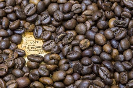 ロースト コーヒー豆の背景によって覆われたコートジボワールのヴィンテージの地図。この国は、主要な生産者およびコーヒーの輸出業者のひとつ 写真素材