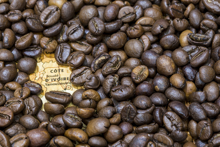 producers: Vintage map of Ivory Coast covered by a background of roasted coffee beans. This nation is one of the main producers and exporters of coffee. Horizontal image. Stock Photo