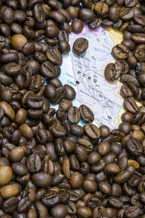 producers: Geographical map of Peru covered by a background of roasted coffee beans. This nation is between the ten main producers and exporters of coffee. Vertical image.