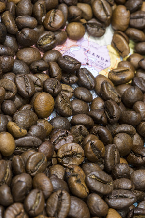 producers: Geographical map of Uganda covered by a background of roasted coffee beans. This nation is one of the main producers and exporters of coffee. Vertical image.