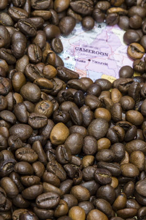 geographical: Geographical map of Cameroon covered by a background of roasted coffee beans. This nation is one of the main producers and exporters of coffee. Vertical image.