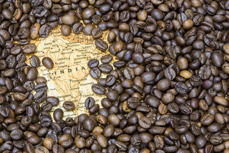 exporter: Vintage map of India covered by a background of roasted coffee beans. This nation is between the six main producers and exporters of coffee. Horizontal image. Stock Photo