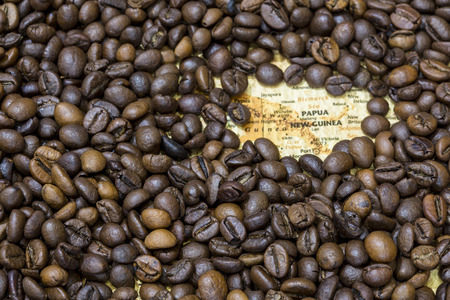 producers: Vintage map of Papua New Guinea covered by a background of roasted coffee beans. This nation is one of the main producers and exporters of coffee. Horizontal image.