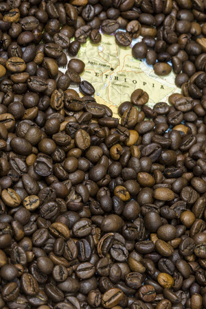 producers: Geographical map of Ethiopia covered by a background of roasted coffee beans. This nation is between the five main producers and exporters of coffee. Vertical image. Stock Photo