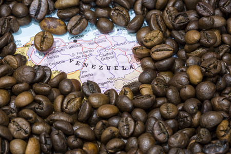 exporter: Geographical map of Venezuela covered by a background of roasted coffee beans. This nation is one of the main producers and exporters of coffee. Horizontal image.