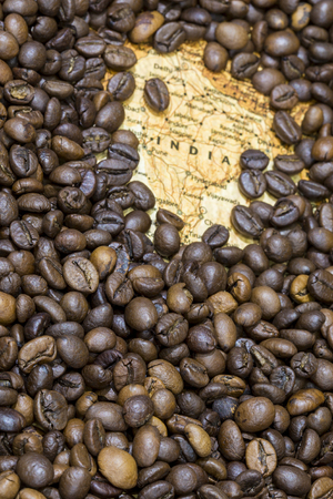 exporter: Vintage map of India covered by a background of roasted coffee beans. This nation is between the six main producers and exporters of coffee. Vertical image.