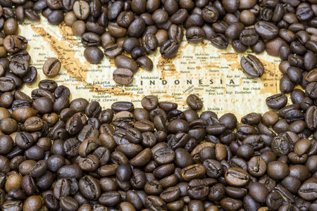 producers: Vintage map of Indonesia covered by a background of roasted coffee beans. This nation is between the five main producers and exporters of coffee. Horizontal image. Stock Photo