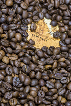 producers: Vintage map of Ethiopia covered by a background of roasted coffee beans. This nation is between the five main producers and exporters of coffee. Vertical image.