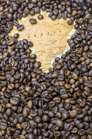 exporter: Vintage map of Brazil covered by a background of roasted coffee beans. This nation is the first main producer and exporter of coffee. Vertical image. Stock Photo