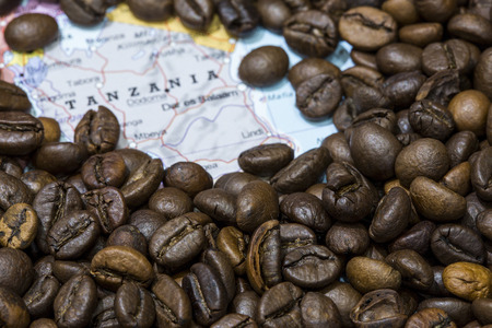 Geographical map of Tanzania covered by a background of roasted coffee beans. This nation is one of the main producers and exporters of coffee. Horizontal image.