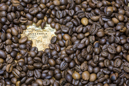 producers: Vintage map of Venezuela covered by a background of roasted coffee beans. This nation is one of the main producers and exporters of coffee. Horizontal image.