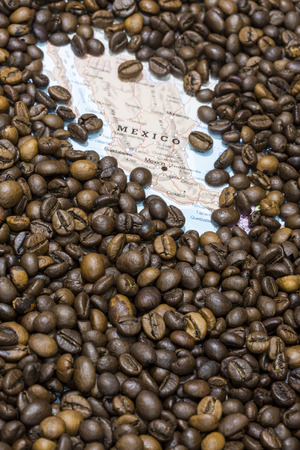 producers: Geographical map of Mexico covered by a background of roasted coffee beans. This nation is between the ten main producers and exporters of coffee. Vertical image.
