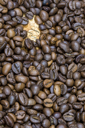 producers: Vintage map of Uganda covered by a background of roasted coffee beans. This nation is one of the main producers and exporters of coffee. Vertical image.