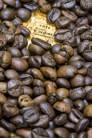 producers: Vintage map of Ivory Coast covered by a background of roasted coffee beans. This nation is one of the main producers and exporters of coffee. Vertical image.