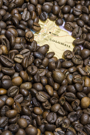 geographical: Geographical map of Colombia covered by a background of roasted coffee beans. This nation is the third main producers and exporters of coffee. Vertical image.