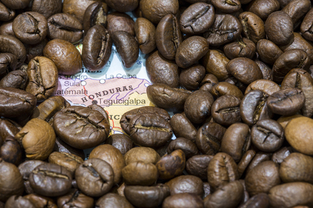 producers: Geographical map of Honduras covered by a background of roasted coffee beans. This nation is between the ten main producers and exporters of coffee. Horizontal image. Stock Photo