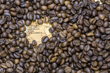 exporter: Vintage map of Colombia covered by a background of roasted coffee beans. This nation is the third main producer and exporter of coffee. Horizontal image.