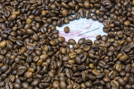 exporter: Geographical map of Papua New Guinea covered by a background of roasted coffee beans. This nation is one of the main producers and exporters of coffee. Horizontal image.