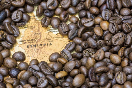 Vintage map of Ethiopia covered by a background of roasted coffee beans. This nation is between the five main producers and exporters of coffee. Horizontal image.