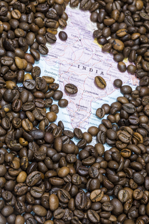 producers: Geographical map of India covered by a background of roasted coffee beans. This nation is between the six main producers and exporters of coffee. Vertical image. Stock Photo