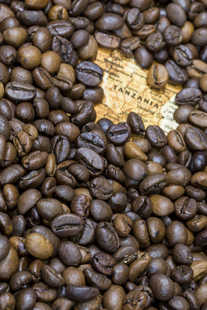 exporter: Vintage map of Tanzania covered by a background of roasted coffee beans. This nation is one of the main producers and exporters of coffee. Vertical image. Stock Photo