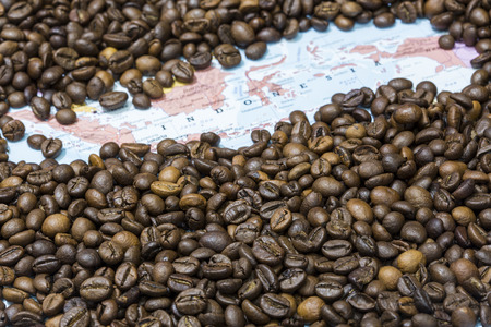 producers: Geographical map of Indonesia covered by a background of roasted coffee beans. This nation is between the five main producers and exporters of coffee. Horizontal image.