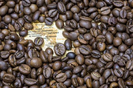 producers: Vintage map of Central America covered by a background of roasted coffee beans. Guatemala, Honduras, Nicaragua, El Salvador and Costa Rica are between the main producers and exporters of coffee.
