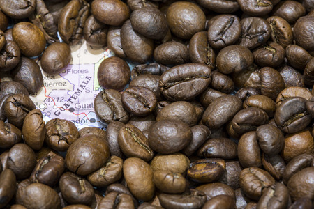 Geographical map of Guatemala covered by a background of roasted coffee beans. This nation is between the ten main producers and exporters of coffee. Horizontal image.