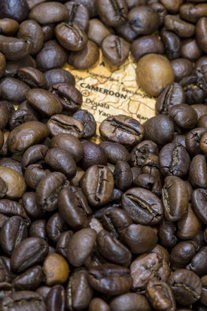 producers: Vintage map of Cameroon covered by a background of roasted coffee beans. This nation is one of the main producers and exporters of coffee. Vertical image. Stock Photo