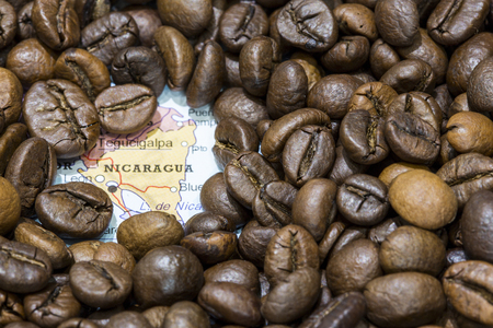 producers: Geographical map of Nicaragua covered by a background of roasted coffee beans. This nation is one of the main producers and exporters of coffee. Horizontal image.