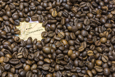 geographical: Geographical map of Colombia covered by a background of roasted coffee beans. This nation is the third main producers and exporters of coffee. Horizontal image.