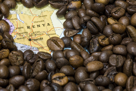 producers: Geographical map of Kenya covered by a background of roasted coffee beans. This nation is one of the main producers and exporters of coffee. Horizontal closeup image.
