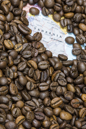 Geographical map of Tanzania covered by a background of roasted coffee beans. This nation is one of the main producers and exporters of coffee. Vertical image.