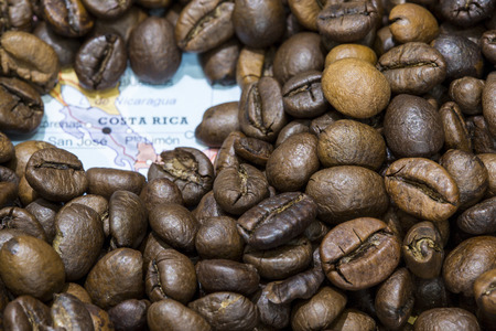 Geographical map of Costa Rica covered by a background of roasted coffee beans. This nation is one of the main producers and exporters of coffee. Horizontal image.