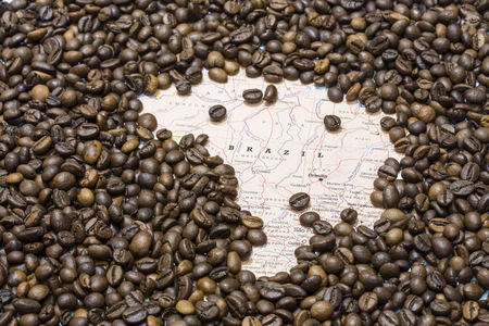 producers: Geographical map of Brazil covered by a background of roasted coffee beans. This nation is the first main producers and exporters of coffee. Horizontal image.
