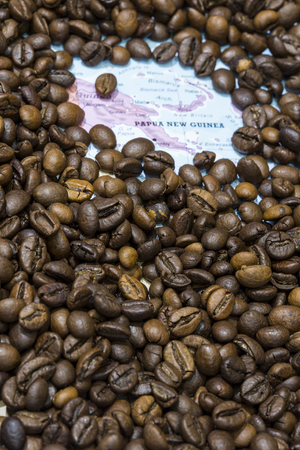geographical: Geographical map of Papua New Guinea covered by a background of roasted coffee beans. This nation is one of the main producers and exporters of coffee. Vertical image. Stock Photo