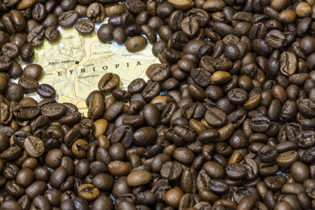 producers: Geographical map of Ethiopia covered by a background of roasted coffee beans. This nation is between the five main producers and exporters of coffee. Horizontal image. Stock Photo