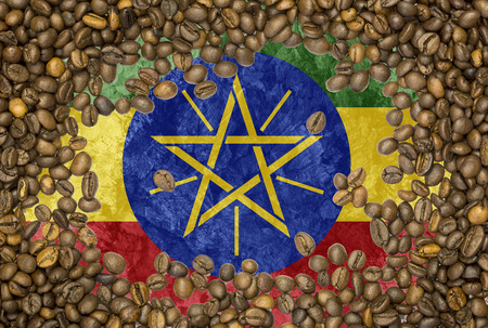 National country flag of Ethiopia under a background of roasted brown coffee beans